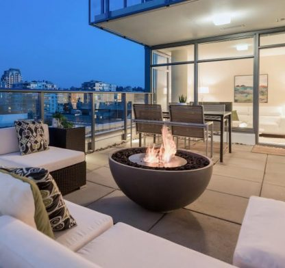 Solus hemi firepit with ethanol biofuel burner on balcony deck overlooking skyline with flames lit