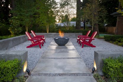 "Solus hemi 36"" fire pit in cinder colour, lit, on formal plaza with red Adirondack chairs"