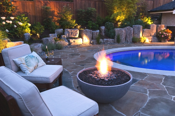 "Solus hemi 36"" firepit lit in cinder colour near circular pool and rock garden"