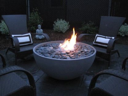 "Solus hemi 36"" fire pit, lit, surrounded by seating and Buddha statue"